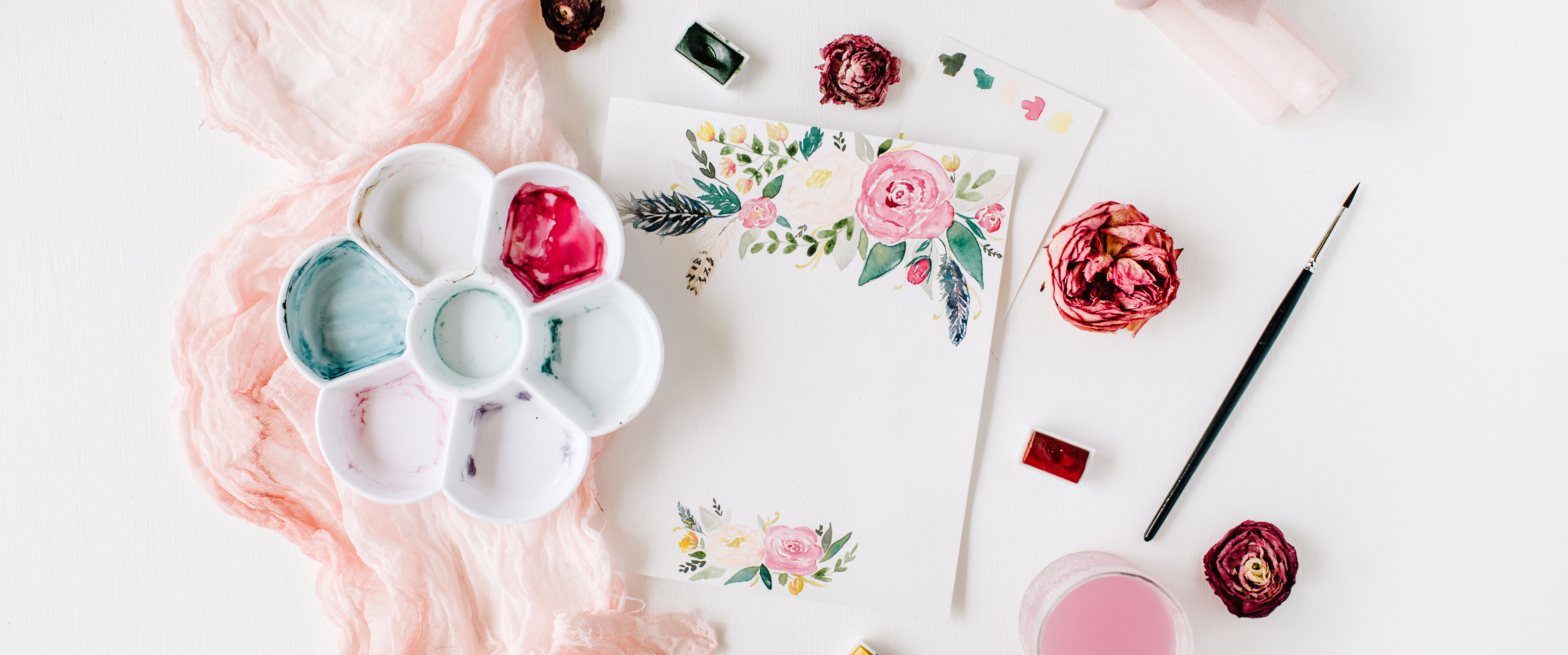 Workspace. Pink and red roses painted with watercolor, paintbrush and roses on white wooden background. Overhead view. Flat lay, top view